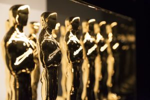 Small oscar award statuettes in a line