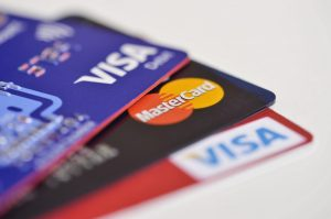 There are three credit cards in a very close-up shot that show the Visa and MasterCard logos