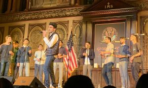 members of penn masala sing on stage at gaston hall