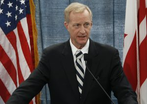 Jack Evans in a black suit stands at a podium between two American flags