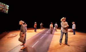 People stand on either side of a painted road running up the center of the stage
