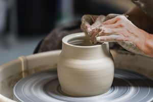 A person sculpting pottery out of clay