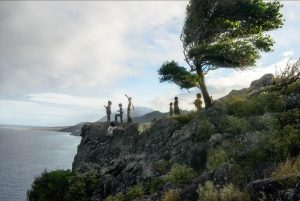 children stand on a cliff looking out on the ocean