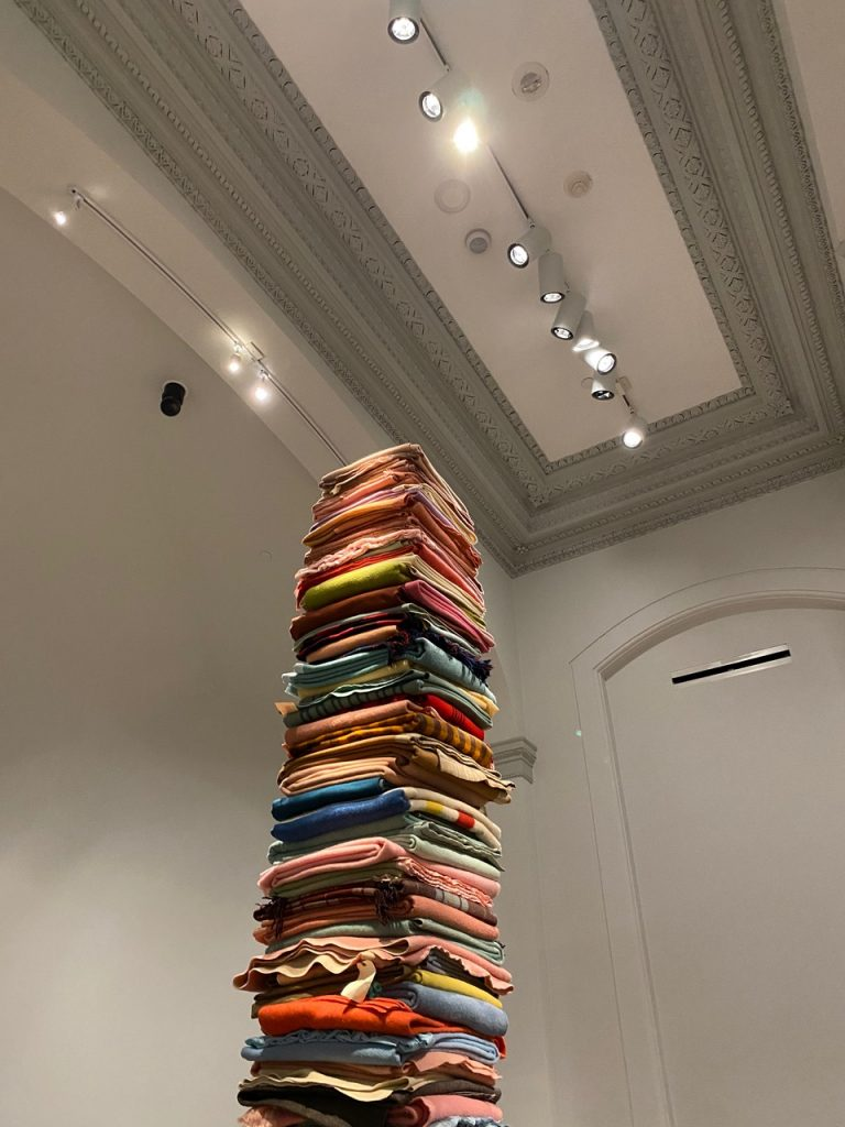 colorful blankets are stacked on top of each other to form a towering pile