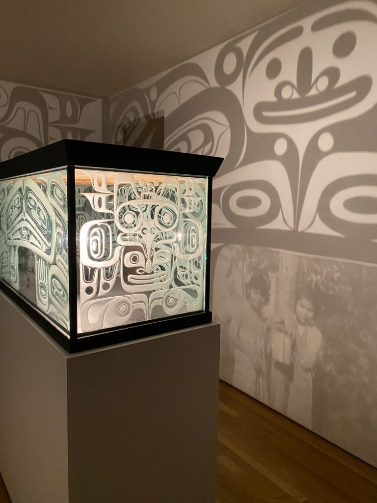 a light box projects shadows of illustrated faces onto the wall