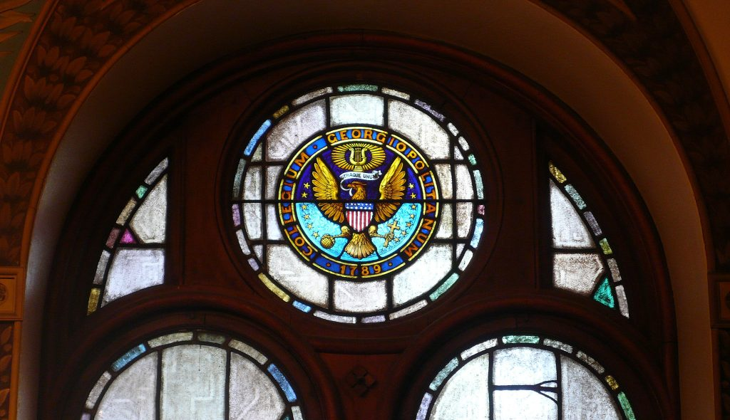 There is the Georgetown Seal and Motto at the top of a stained glass window