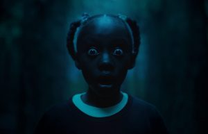 This is a dark image of a young girl staring at the camera in shock and horror