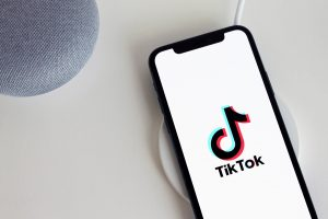 iPhone on wireless charger displays tik tok loading screen there is a speaker in the upper left corner