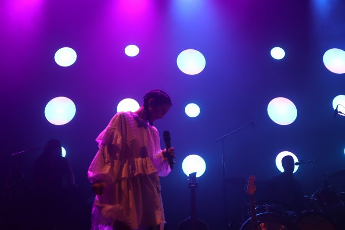 Michelle Zauner looks down in a white dress singing at the Fillmore Silver Spring on July 21.